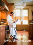 A man is standing in his kitchen leaning against the stove reading the morning news paper and holding a glass of orange juice in his hand.  He is wearing a white bath robe.